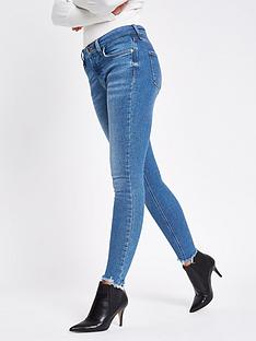 da585ba8fed29a River Island River Island Amelie Regular Leg Chewed Hem Super Skinny Jeans  - Mid Blue